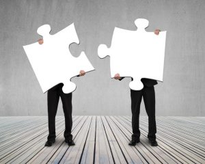 Businessmen holding two puzzles to connect